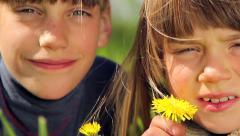 Europeans boys in a meadow of green grass smelling a flower, dandelion Stock Footage