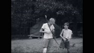 Boy campers playing with bow and arrow at campsite Stock Footage