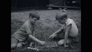 Boy campers playing board game at campsite Stock Footage