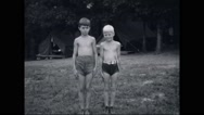 Two shirtless boy campers posing and walking hand in hand at campsite Stock Footage
