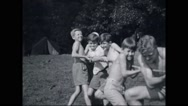 Boy campers playing tug-of-war at campsite Stock Footage