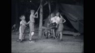 Boy campers playing with rope at campsite Stock Footage