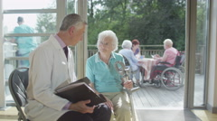 4K Caring doctor discussing medical notes with elderly female patient Arkistovideo