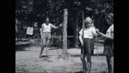 Girl campers aiming with bow and arrow at campsite Stock Footage