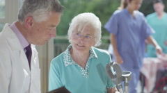 4K Caring doctor discussing medical notes with elderly female patient - stock footage