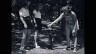 Girl campers feeding a puppy at campsite Stock Footage