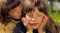 Portrait of boy outdoors. The boy whispers something in the ear of his friend. Stock Footage