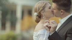 Bride and groom show their wedding rings, kiss and look into each other's eyes - stock footage