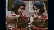 Close-up of school girls reading forest fire prevention comics Stock Footage