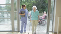 4K Caring nurse helping elderly female patient to walk in hospital or care home - stock footage