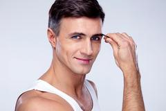 Happy man removing eyebrow hairs with tweezing Stock Photos
