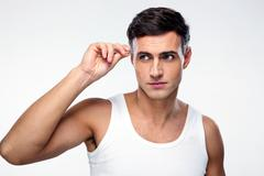handsome man removing eyebrow hairs with tweezing - stock photo