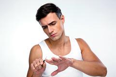 Man doing manicure over gray background Stock Photos