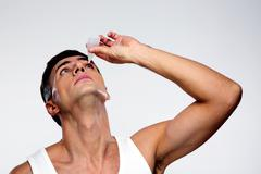 Handsome man applying eye drop over gray background Stock Photos