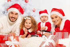 Family of four with presents and christmas tree Stock Photos