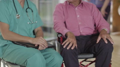 4K Caring male nurse giving support to elderly male patient in a wheelchair - stock footage