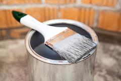 Paint brush in grey color laying on can Stock Photos