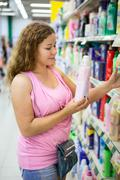 woman customer looking at conditioner for linen in shop - stock photo
