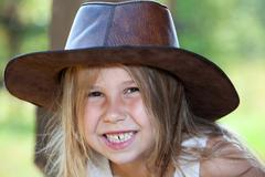 Toothy smile of young pretty girl in cowboy hat, facial portrait Stock Photos