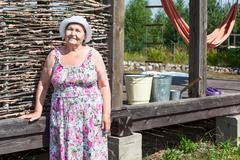 Joyous senior woman standing near house wall Stock Photos