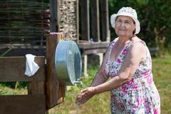 Stock Photo of mature woman washs her hands at country residence