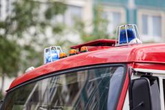 two blue flashing lights on the roof of fire truck - stock photo