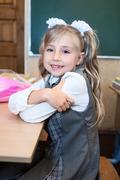 Smiling first grade schoolgirl portrait, girl in uniform - stock photo