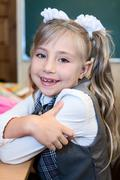 Stock Photo of Smiling first grade schoolgirl portrait, Caucasian girl smiling and looking at c
