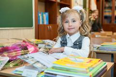 First grade pupil a girl sitting at school desk at lesson in classroom - stock photo