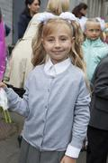 First grade pupil a girl standing outdoor at school yard - stock photo
