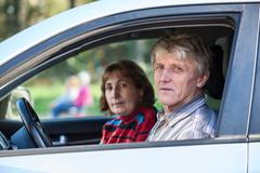 senior husband and wife sitting in land vehicle, looking through the window - stock photo