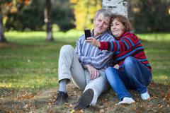 mature man and woman sitting under tree and smiling when making selfie - stock photo