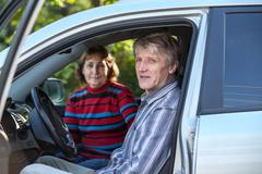 mature husband and wife sitting in land vehicle, looking through the opened d - stock photo