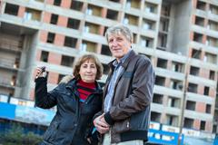 Stock Photo of satisfied old age couple showing house keys standing against building under c