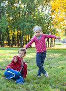 young boy sitting grass, showing thumb up and pretty girl thump down in autum - stock photo