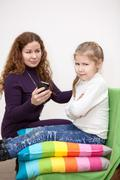 Child with displeasure giving smartphone mother Stock Photos