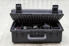 bit open plastic case on floor with photo equipments in dividers - stock photo