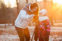 mother and child set up the camera on tripod in the rays of setting sun - stock photo