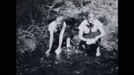 Girl campers washing plates in stream Stock Footage