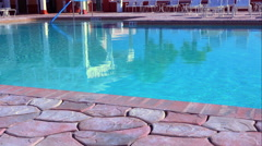Swimming pool with stone tile deck Stock Footage