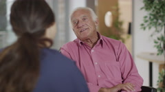 4K Caring nurse giving support to elderly male patient in a wheelchair - stock footage