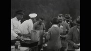 General Billy Mitchell talking to guest at barbeque counter Stock Footage