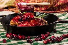 Two cranberry glazed chicken breasts in pan Stock Photos