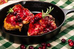 Two cranberry glazed chicken breasts in skillet Stock Photos