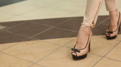 Slender female legs in shoes stepping on the floor Stock Footage