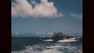 Marine corps carrying dead bodies in PT boat and looking at navy aircraft in sky Stock Footage