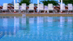 Lounge chairs  around swimming pool Stock Footage