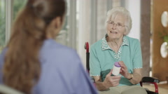 4K Caring doctor or nurse advising elderly female patient on her medication Stock Footage