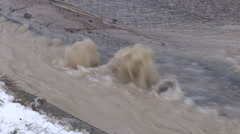 Water main break with water gushing on city street on cold winter day Stock Footage