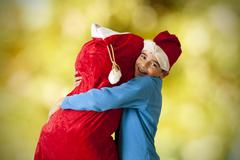 children with sack of gifts santa claus - stock photo